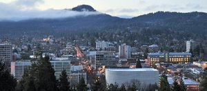 Photo of Eugene, Oregon, USA showing butte and clouds in background behind downtown.